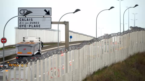 fence secures the main motorway into calais port to prevent migrants climbing on trucks on january 07, 2019 in calais, france. in recent weeks there... - eurotunnel folkestone stock-videos und b-roll-filmmaterial