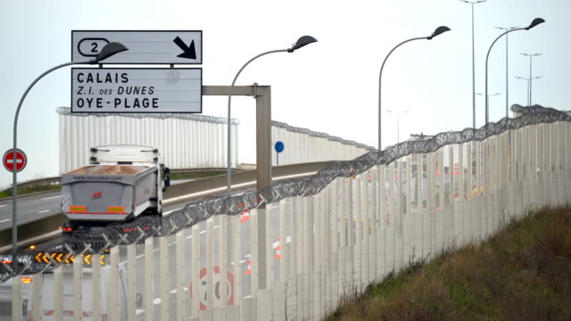 a fence secures the main motorway into calais port to prevent migrants climbing on trucks on january 07 2019 in calais france in recent weeks there... - calais stock videos and b-roll footage