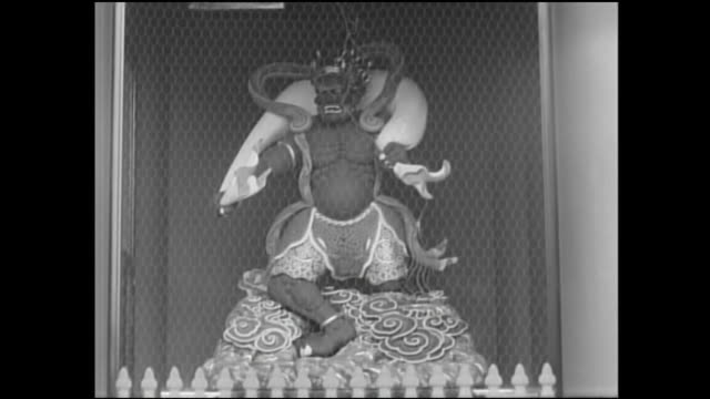 A fence surrounds a statue of Raijin