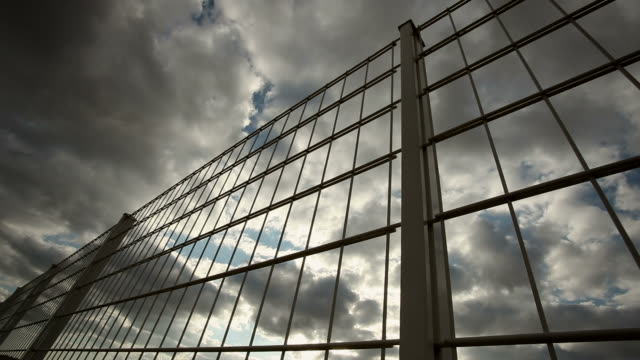 fence with clouds - close up - fence stock videos & royalty-free footage