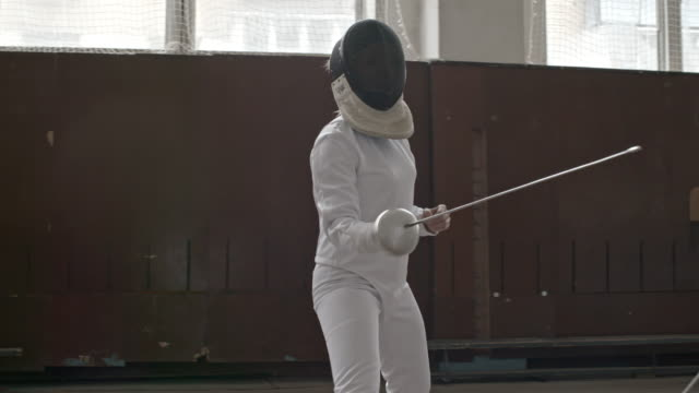 Fencer attacking opponent while training in gym