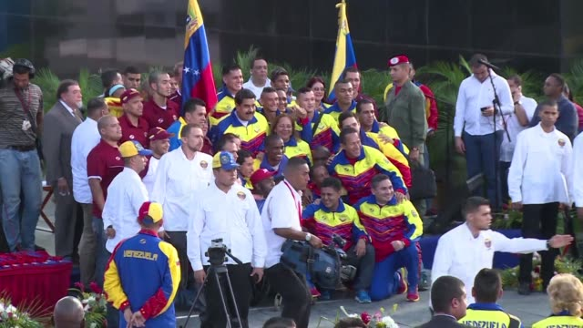 Fencer Ruben Limardo a gold medalist in the 2012 London Games receives the Venezuelan national flag Monday in Caracas during a ceremony with the...