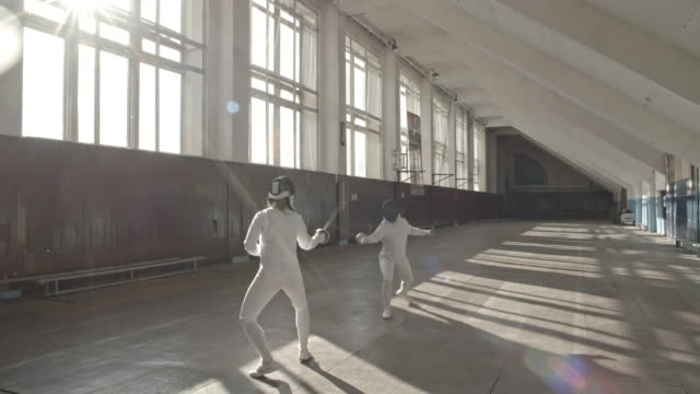 vídeos y material grabado en eventos de stock de fencing athletes fighting with foils - en guardia