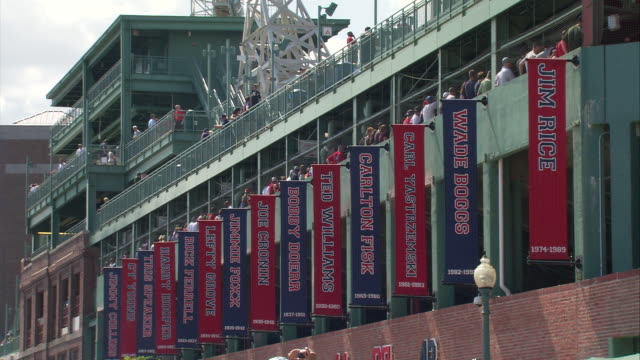 ms fenway park exterior during game, banners hanging on stadium side displaying names of past great red sox players / boston, massachusetts, usa - scrittura occidentale video stock e b–roll