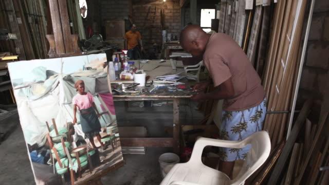 Ferol Hughes Berthin works to restore an earthquake damaged Franck Louissant painting at Nadar Art Gallery.