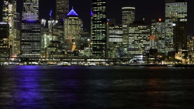 ws t/l zo ferries and other boats moving at circular quay in front of skyscrapers at sydney harbour / sydney, new south wales, australia - 夜遊び点の映像素材/bロール