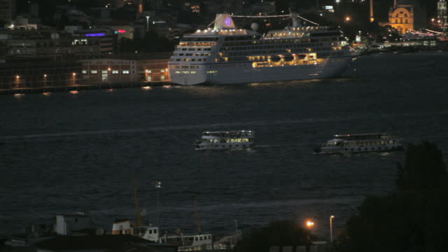 HA Ferries and tour boats floating past moored cruise ship in the busy Bosphorus strait / Istanbul, Turkey