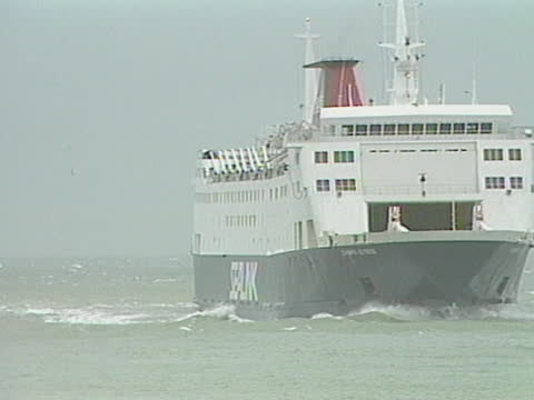 vidéos et rushes de ferries arrive in calais harbor there is a medium depth of field shot of a ferry sailing in the harbor. the camera slightly pans right with the ferry... - sport
