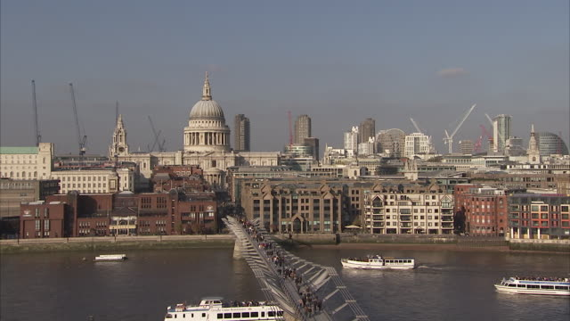 Ferries cruise down the River Thames under the Millennium Bridge. Available in HD.