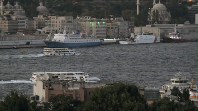 ts ferries cruising down the bosphorus strait, passing moored boats, ortakoy mosque, and hillside buildings / istanbul, turkey - ortakoy mosque stock videos and b-roll footage
