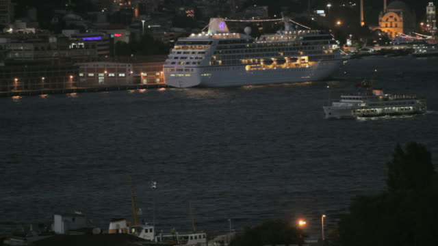 HA Ferries sailing past moored and illuminated cruise ship in Bosphorus strait / Istanbul, Turkey