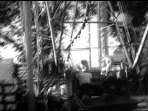 vidéos et rushes de ferris wheel amusement ride gondolas lowering on wheel ws children adults riding ms young boy standing next to female body in fairground eating... - 1952