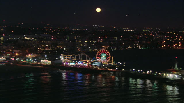 vídeos de stock e filmes b-roll de aerial ferris wheel and amusement park illuminated on the pier at night, with a full moon beyond/ santa monica, california, united states - santa monica