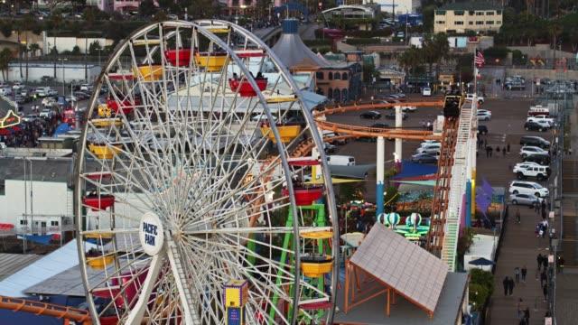 ferris wheel and roller coaster on santa monica pier - aerial - santa monica city stock videos & royalty-free footage