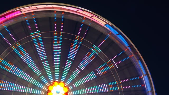ferris wheel at an amusement park turning during the night - school fete stock videos and b-roll footage