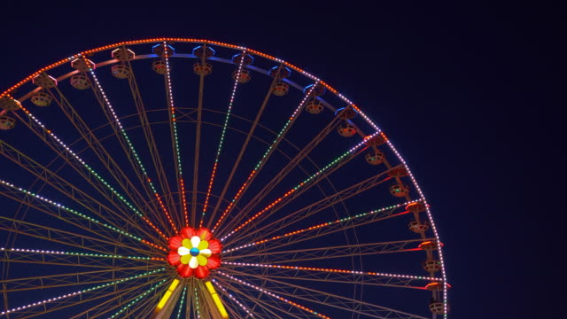 ferris wheel at an amusement park turning during the night - ferris wheel stock videos & royalty-free footage
