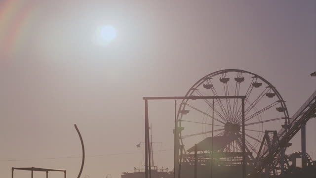 WS Ferris wheel in Pacific Park hanging still against blazing sunset, with bicyclist riding in circles / Santa Monica, California, United States