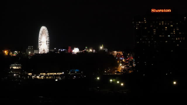ferris wheel in the canadian side of tourist resorts of the niagara falls at night - river niagara stock videos & royalty-free footage