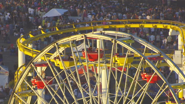 WS AERIAL POV Ferris Wheel On Santa Monica Pier during sunset at Santa Monica, California
