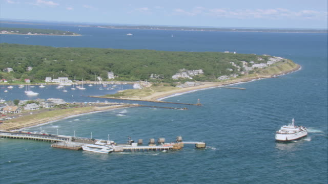 AERIAL Ferry approaching long jetty on peninsular coastline with trees and village / Oak Bluffs, Massachusetts, United States