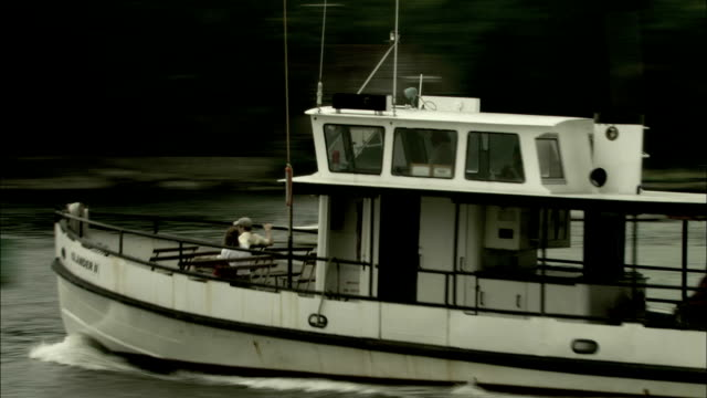 a ferry boat cruises past a pier and through a harbor. available in hd. - ferry stock videos & royalty-free footage
