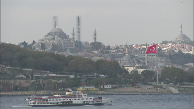stockvideo's en b-roll-footage met a ferry boat passes the blue mosque. - istanboel