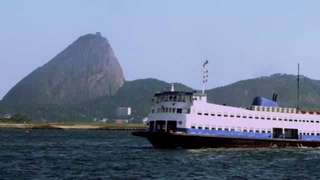 vídeos de stock e filmes b-roll de ferry boat passing in front of sugar loaf mountain - 50 segundos ou mais