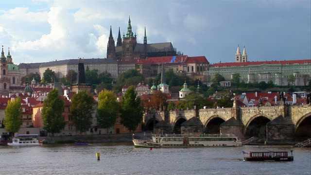 A ferry boat sails in the Vltava River near St. Vitus Cathedral and Prague Castle in Prague, Czech Republic.