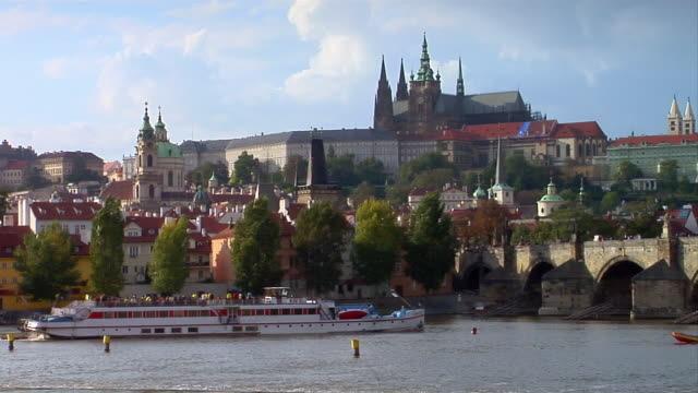 A ferry boat sails on the Vltava River near the St. Vitus Cathedral and Prague Castle in Prague, Czech Republic.