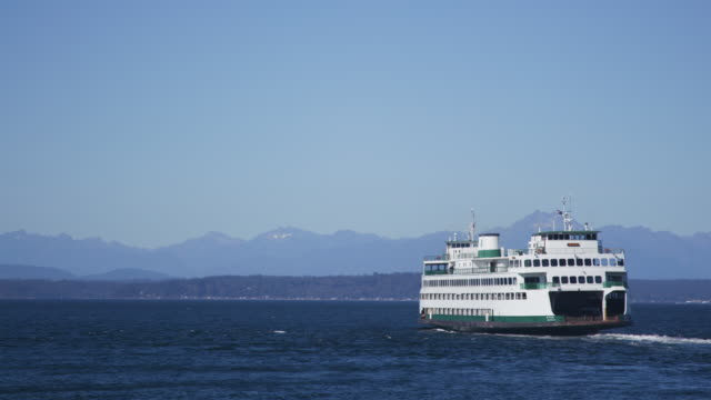 Ferry boat sails on water, mountains in background