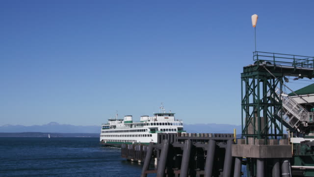 ferry boat sails out into water, washington state - nordpazifik stock-videos und b-roll-filmmaterial