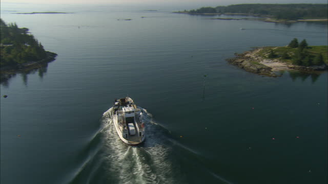 vidéos et rushes de low aerial, ferry boat traveling along coastline, vinalhaven, maine, usa - maine