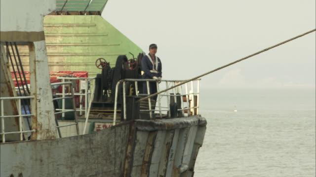 ws ferry boat worker standing on deck of ferry with attached rope, yuhuan county, zhejiang, china - förtöjd bildbanksvideor och videomaterial från bakom kulisserna