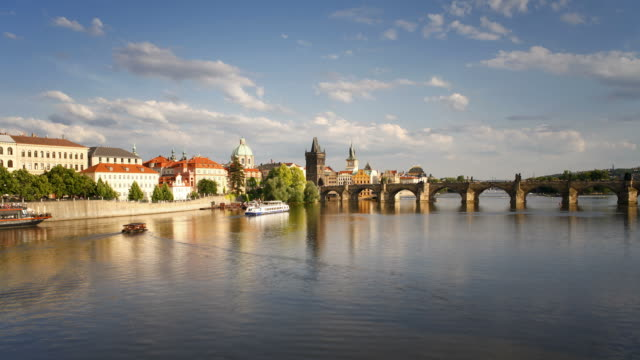 ferry boats move beneath the charles bridge on the river vltava near prague castle. - river vltava stock videos & royalty-free footage