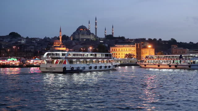 ws ferry boats on golden horn with new mosque (yeni mosque) and suleymaniye mosque in background at dusk / istanbul, turkey - yeni cami mosque stock videos and b-roll footage