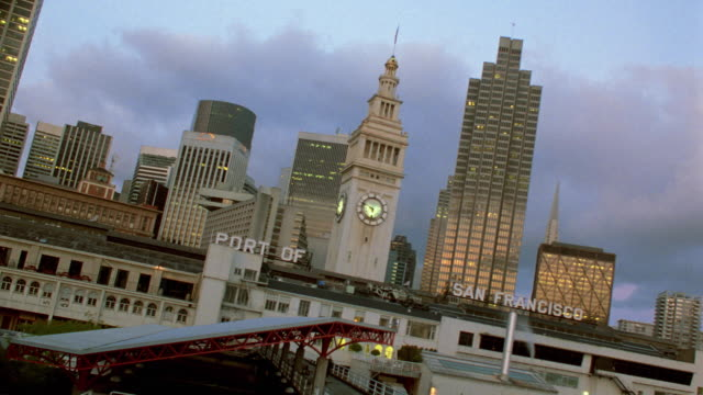canted ferry building at port of san francisco + skyline at dusk / california - san francisco ferry building stock videos & royalty-free footage