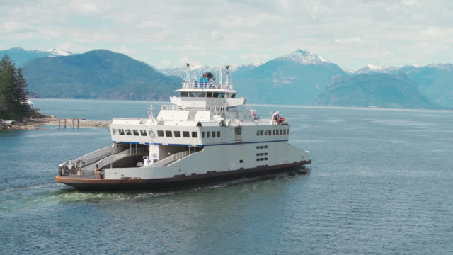 ferry crossing horseshoe bay in the sunny day, in front of mountains covered by snow. vancouver, british columbia, canada. - ferry stock videos & royalty-free footage