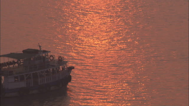 a ferry cruises by the harbour as the sunset is reflected in the water mumbai available in hd. - vagare senza meta video stock e b–roll