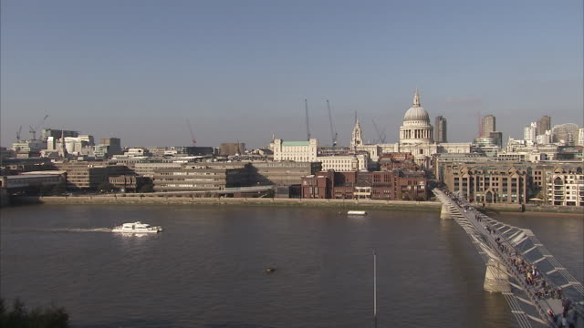 A ferry cruises down the River Thames and under the Millennium Bridge. Available in HD.