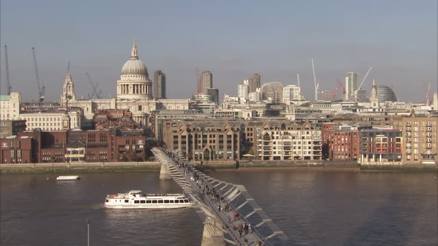 A ferry cruises down the River Thames under the Millennium Bridge. Available in HD.