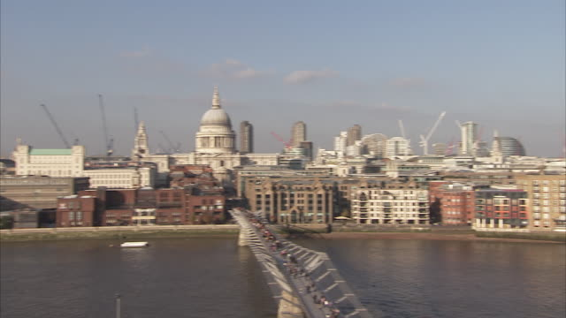 A ferry cruises the River Thames as pedestrians walk across the Millennium Bridge. Available in HD.
