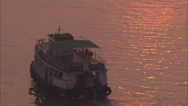a ferry cruises through the harbour as the sunset is reflected in the water mumbai available in hd. - vagare senza meta video stock e b–roll