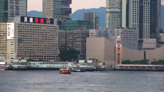 ferry in front of kowloon skyline in hong kong - tsim sha tsui stock videos & royalty-free footage