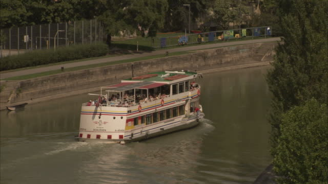 a ferry moves along a river near the riesenrad ferris wheel in vienna, austria. available in hd - prater park stock videos & royalty-free footage