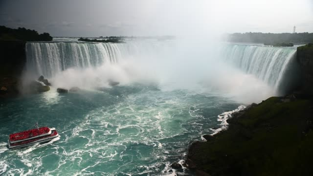 vídeos de stock, filmes e b-roll de a ferry moves closer to the waterfall at niagara falls in ontario canada shot on the 16th of october 2014 - niagara falls