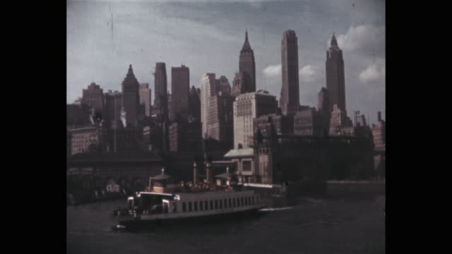 ferry moving in front of lower manhattan skyline, new york city, ny, usa - porto di new york video stock e b–roll