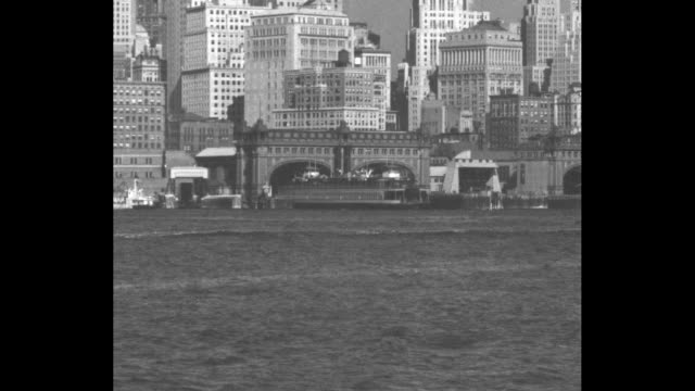 ferry moving on river lower manhattan skyline in bg / docked ferry / ferry passing camera tugboat passing in opposite direction buildings in bg /... - river east stock videos & royalty-free footage