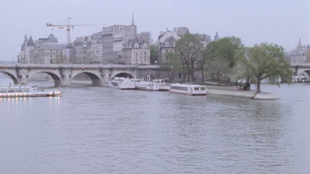 vidéos et rushes de a ferry on the seine river approaches a small island. - île