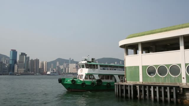 a ferry operated by new world first ferry services limited can be seen crossing victoria harbor in hong kong china the skyline of the north point... - central plaza hong kong stock videos & royalty-free footage