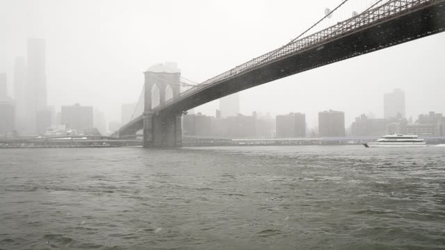 vídeos de stock, filmes e b-roll de a ferry passes under the brooklyn bridge as it makes its way along the east river during a snowstorm march 21 2018 in new york city the fourth... - atlântico central eua